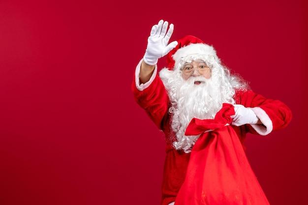 Vista frontale della borsa di apertura di babbo natale piena di regali per i bambini durante le vacanze di emozione natalizia rossa