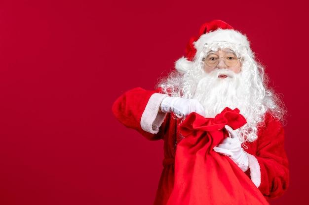 Vista frontale babbo natale che apre la borsa rossa piena di regali per i bambini in vacanza rossa emozione di natale