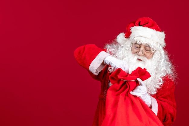 Vista frontale babbo natale che apre la borsa rossa piena di regali per i bambini durante le emozioni natalizie delle vacanze rosse