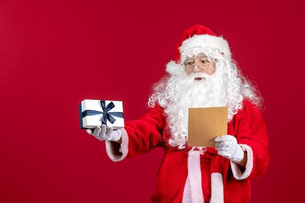 Вид спереди санта-клауса, читающего письмо от ребенка и держащего подарок на рождественский праздник красной эмоции