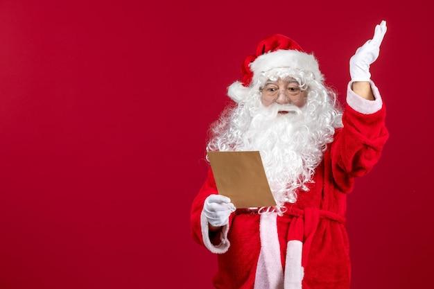 Вид спереди санта-клауса, читающего письмо от ребенка на красном подарке, рождественский праздник эмоции