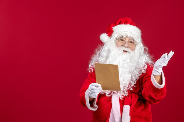 Front view santa claus reading letter from kid on red present xmas holiday emotions