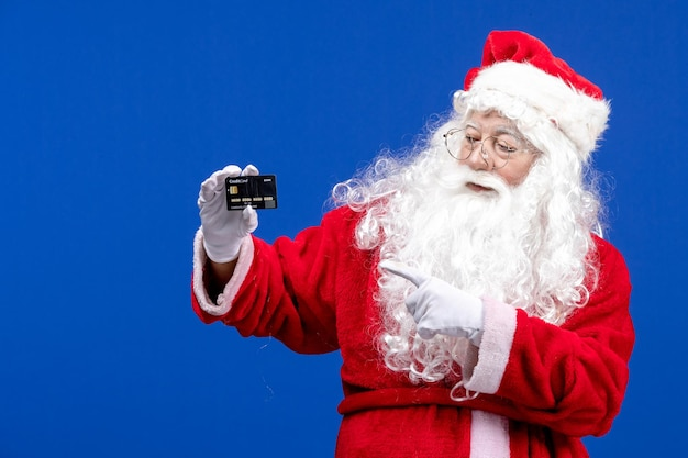 Vista frontale babbo natale in abito rosso in possesso di carta di credito su blu presente natale colori vacanza