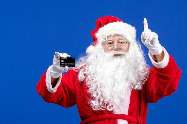Vista frontale babbo natale in abito rosso con carta di credito nera sul regalo di natale blu colore