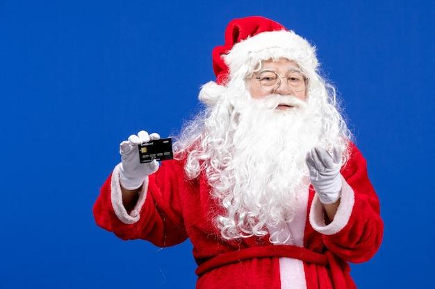 Vista frontale babbo natale in abito rosso con carta di credito nera su vacanze di colore natalizio blu presenti