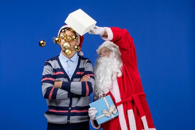 青いクリスマス休暇の感情で若い男性におもちゃを投げる正面のサンタクロース