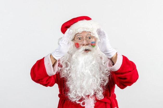 Front view of santa claus with azerbaijani and turkish flag paints on his face on a white wall
