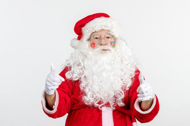 Front view of santa claus with azerbaijani and turkish flag paints on his face on white wall