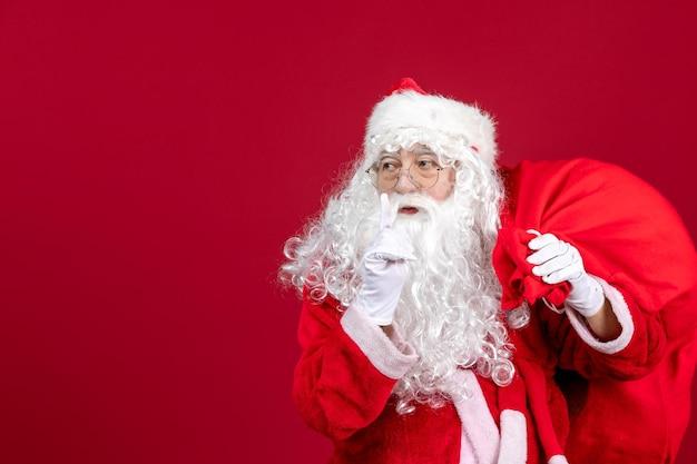 赤い休日の新年のクリスマスの感情のプレゼントでいっぱいのバッグと正面のサンタクロース