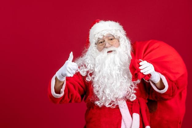 赤い床の休日の新年のクリスマスの感情のプレゼントでいっぱいのバッグと正面のサンタクロース