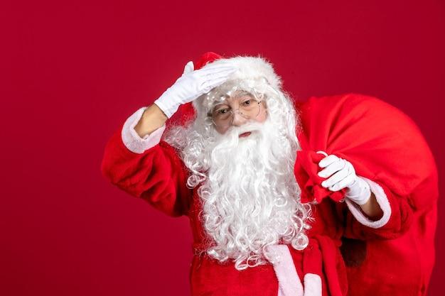 赤い感情の休日の新年のクリスマスのプレゼントでいっぱいのバッグと正面のサンタクロース