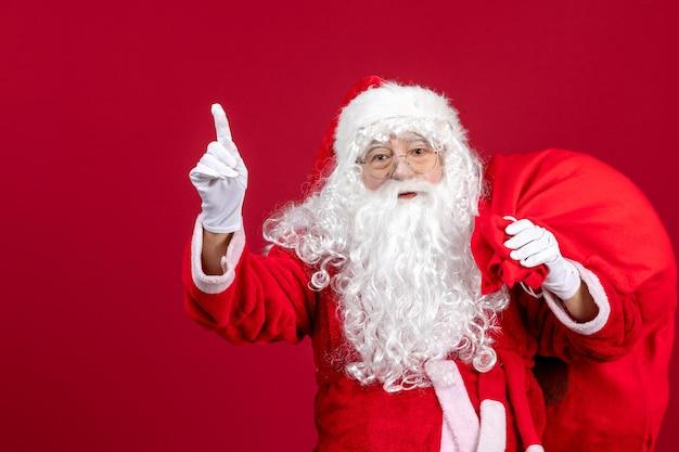 赤い休日の新年のプレゼントでいっぱいのバッグと正面のサンタクロース
