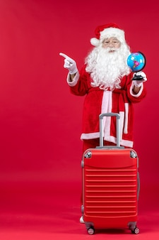 Front view of santa claus with bag holding little globe and preparing for trip on red wall
