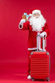 Front view of santa claus with bag holding tickets and preparing for trip on a red wall