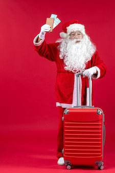 Front view of santa claus with bag holding tickets and preparing for trip on red wall