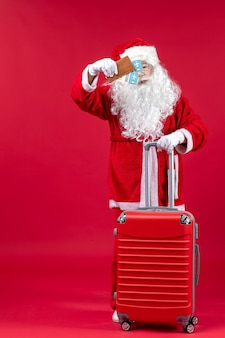 Front view of santa claus with bag holding tickets and preparing for trip on the red wall