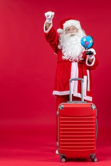 Front view of santa claus with bag preparing for trip on a red wall