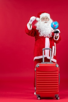 Front view of santa claus with bag preparing for trip on red wall