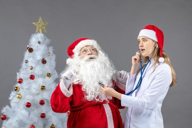 Vista frontale di babbo natale con dottoressa che sta controllando le sue condizioni di salute sul muro grigio
