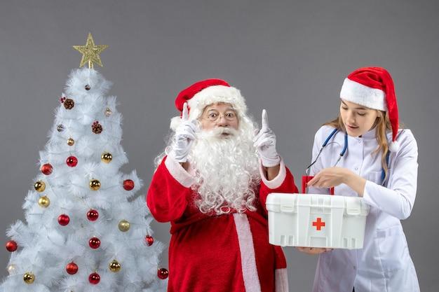 Vista frontale di babbo natale con dottoressa che tiene il kit di pronto soccorso sul muro grigio