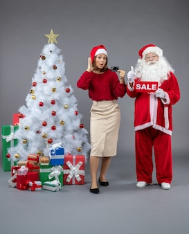 Front view of santa claus with female holding bank card and sale writing on a grey wall
