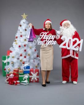 Vista frontale di babbo natale con holding femminile e felice anno nuovo shopping bagss sul muro grigio