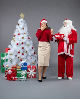 Front view of santa claus with female holding sale writing and bank card on a grey wall