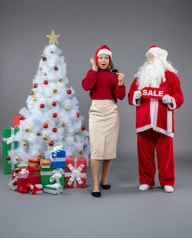 Front view of santa claus with female holding sale writing and bank card on grey wall