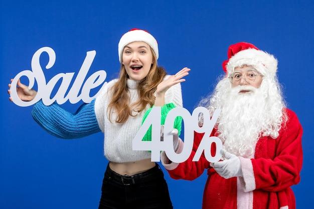 青い休日の寒いクリスマス新年の雪の上の販売の執筆を保持している女性と正面図のサンタクロース
