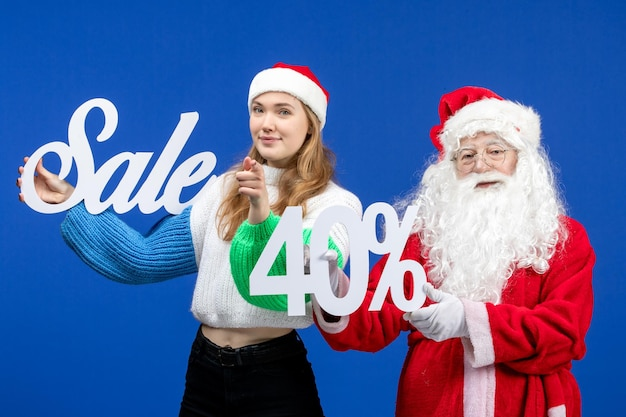 블루 데스크 휴일 추운 크리스마스 새해 눈에 판매 글을 들고 여성과 전면보기 산타 클로스