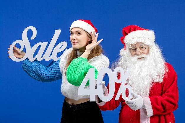 青い床の休日の寒いクリスマス新年の雪にセールの執筆を保持している女性と正面図のサンタクロース