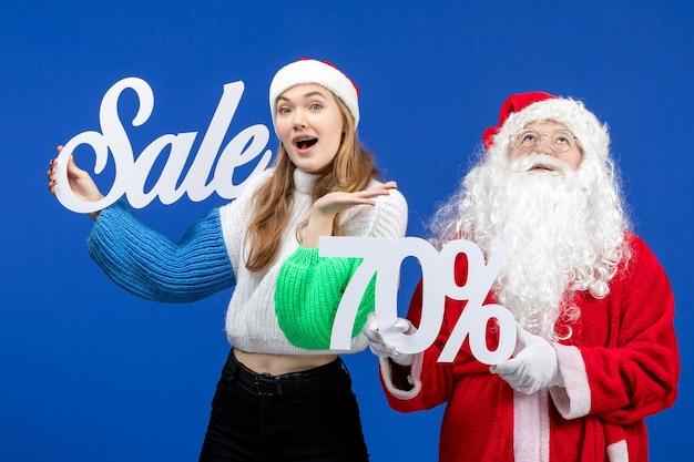 青い休日の寒いクリスマスの新年の雪の買い物のセールの執筆を保持している女性と正面図のサンタクロース