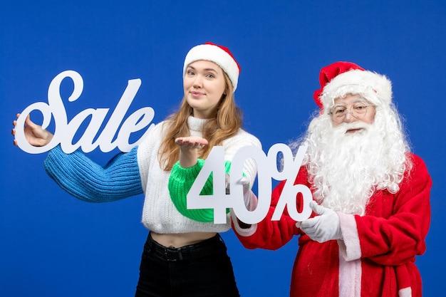 青い休日の寒いクリスマスの新年にセールの執筆を保持している女性と正面図のサンタクロース
