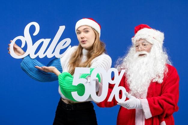 青い休日の寒いクリスマスの新年の雪の上の販売の執筆を保持している女性と正面図のサンタクロース