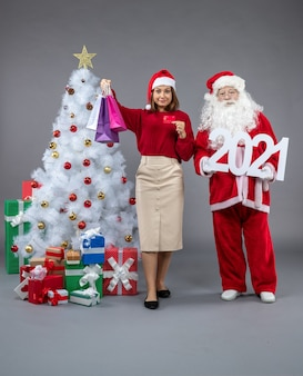 Front view of santa claus with female holding shopping bags and 2021 banner on grey wall