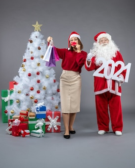 Front view of santa claus with female holding shopping bags and bank card on a grey wall