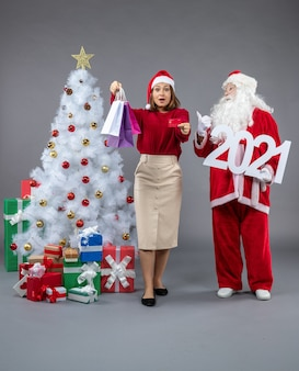 Front view of santa claus with female holding shopping bags and bank card on grey wall
