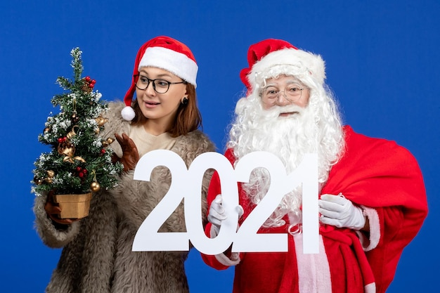 Front view santa claus with female holding writing and little christmas tree on blue color new year