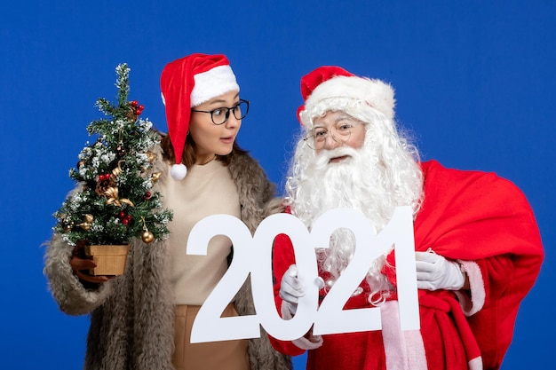 Front view santa claus with female holding writing and little christmas tree on blue colors new year