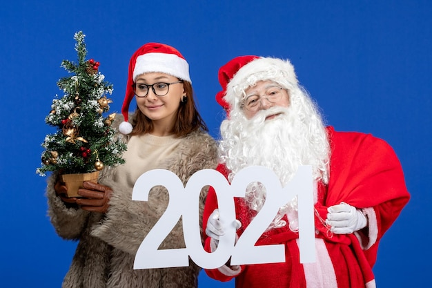 Front view santa claus with female holding writing and little christmas tree on blue new year color