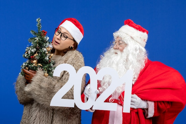 Front view santa claus with female holding writing and little christmas tree on blue new year holiday