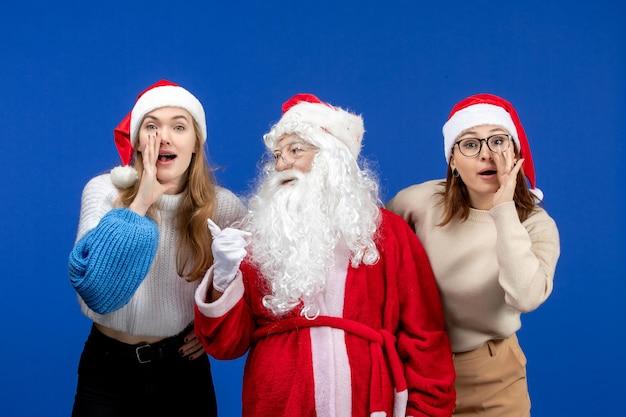 青い色の感情の雪の新年のクリスマスにささやく女性と正面のサンタクロース