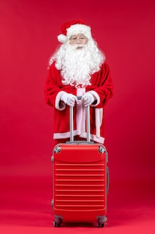 Front view of santa claus with his red bag on a red wall