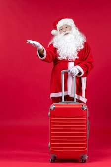 Front view of santa claus with his red bag on red wall