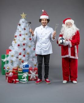 Vista frontale di babbo natale con cuoco maschio intorno a regali di natale eccitato sul muro grigio
