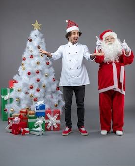 Vista frontale di babbo natale con cuoco maschio intorno a regali di natale sul muro grigio