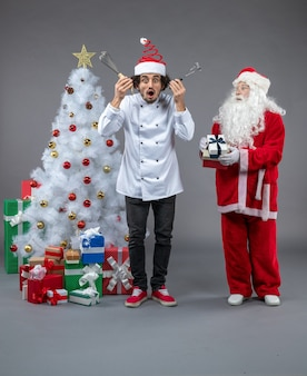 Front view of santa claus with male cook around christmas presents on the grey wall