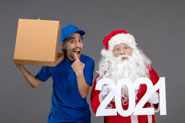 Front view of santa claus with male courier holding 2021 banner and food box on grey wall