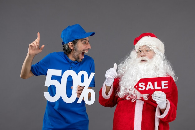 Front view of santa claus with male courier holding 50% and sale banners on grey wall