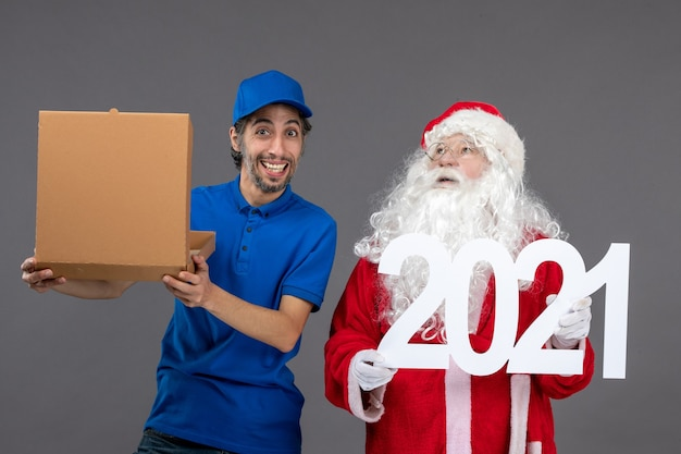 Front view of santa claus with male courier holding food box and on a grey wall